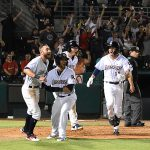 The Missions celebrate at the plate after Jake Hager scored the winning run in the ninth inning in the Missions' 6-5 victory over the Redbirds on Tuesday at Wolff Stadium. - photo by Joe Alexander