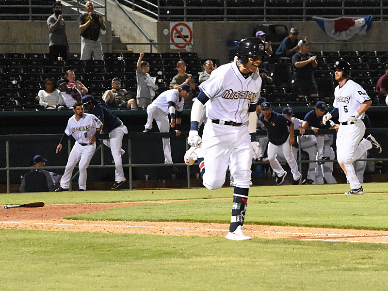 Mauricio Dubon celebrates on his way to first base as Cory Spangenberg (background) comes home with the winning run in the Missions' 6-5 victory over the Memphis Redbirds on Wednesday at Wolff Stadium. - photo by Joe Alexander