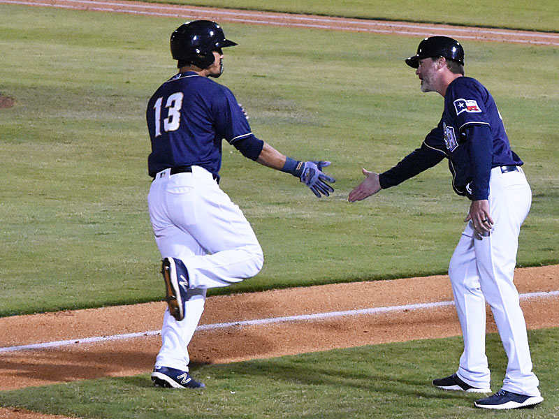 Tyler Saladino is congratulated by third base coach Ned Yost IV as Saladino rounds the bases after hitting his second home run of the game Saturday against the Sounds at Wolff Stadium. - photo by Joe Alexander