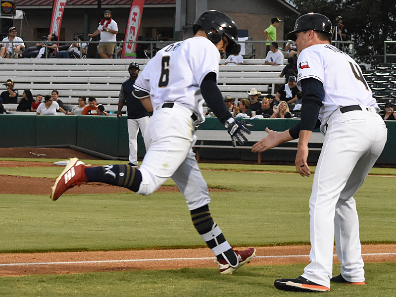Nate Orf is congratulated by Missions third base coach Ned Yoast IV after hitting a leadoff home run Saturday night at Wolff Stadium. - photo by Joe Alexander