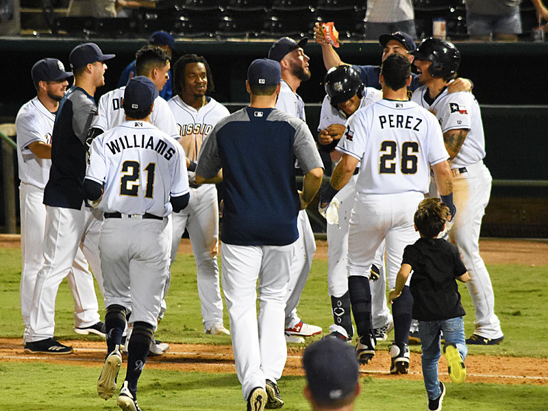 The Missions celebrate after Jacob Nottinham scored the winning run on a ground ball by Trent Grisham on Tuesday at Wolff Stadium. - photo by Joe Alexander