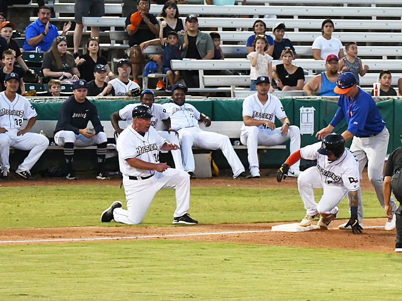 The Missions' Juan Fernandez slides into third with a triple in front of San Antonio manager Phillip Wellman and the Missions' bullpen pitchers in Saturday's victory over the Midland RockHounds at Wolff Stadium. - photo by Joe Alexander