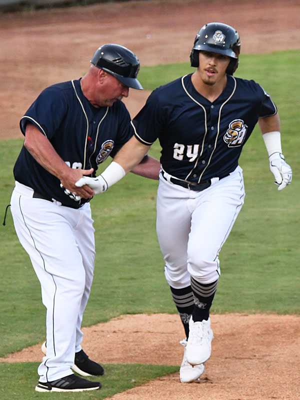 Michael Curry is congratulated by third base coach/manager Phillip Wellman after hitting a home run for the Missions' first run on Friday at Wolff Stadium. - photo by Joe Alexander