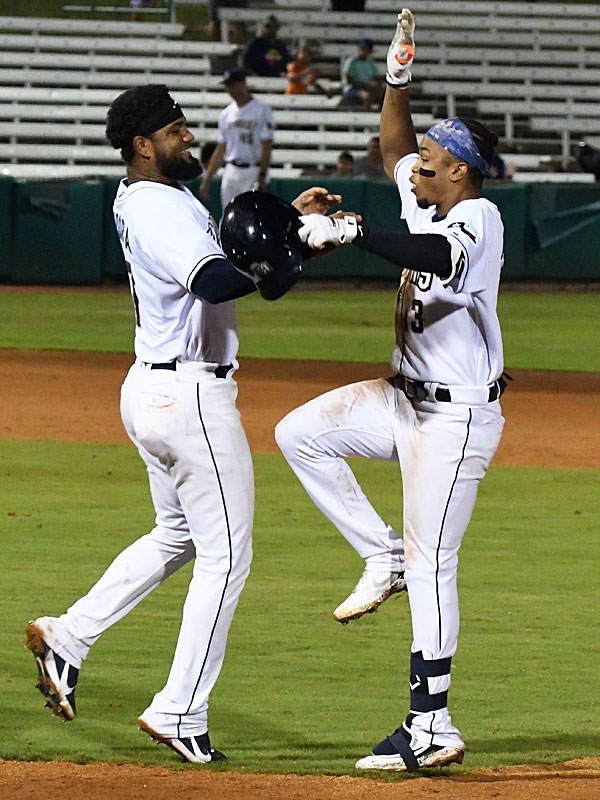 Allen Cordoba (left) and Jose Azocar celebrate after Azocar drove in Cordoba with the winning run with two outs in the 10th inning as the San Antonio Missions beat the Amarillo Sod Poodles 5-4 on Tuesday at Wolff Stadium. - photo by Joe Alexander