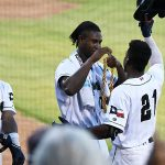 San Antonio Missions outfielder Dwayna Williams-Sutton (21) homered and receives the swag chain from Henry Henry on Sunday at Wolff Stadium. - San Antonio Missions